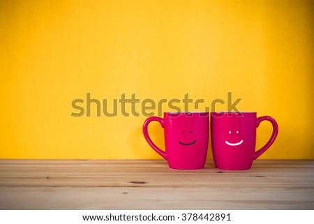 Two cups of coffee and stand together to be heart shape on yellow background with smile face on cup. - stock photo
