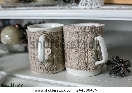 Two cups of coffee in knitted covers, warmth and comfort in winter - stock photo