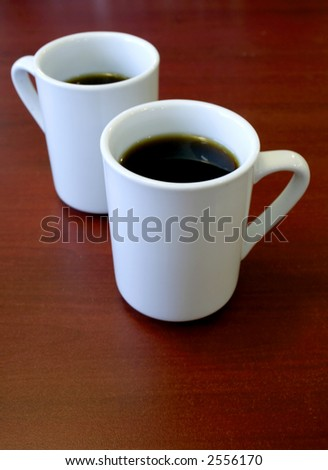 Two cups of coffee in white mugs on a wooden table. - stock photo