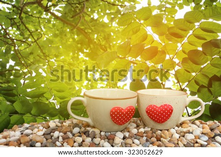 two cups of coffee on pebble ground with leaf on tree ,orange and yellow light background - stock photo