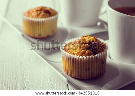 Two cups of coffee on plates next to a chocolate crunches muffins on a wooden table - stock photo