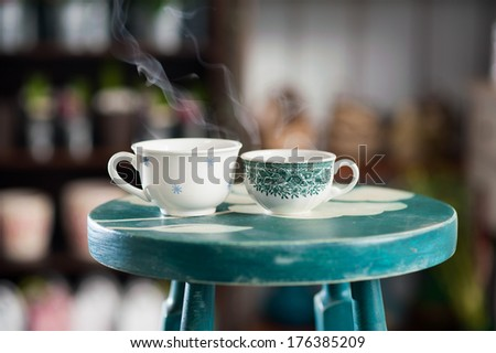Two cups of coffee, steaming hot on a table - stock photo