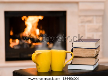 Two cups of coffee with books on the background of the fireplace - stock photo