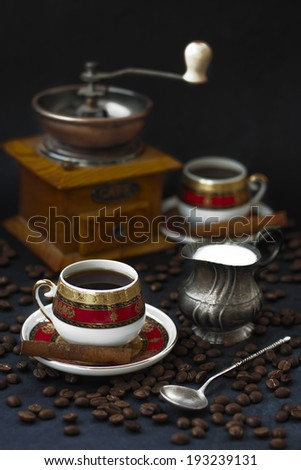 Two cups of coffee with copper coffee mill and silver milk jug - stock photo