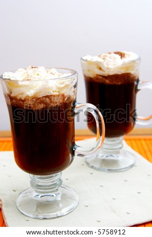 Two cups of coffee with cream and chocolate sprinkles on a orange placemat - stock photo