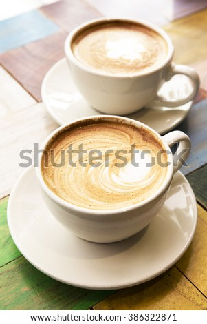 Two Cups of coffee with latte art on wooden table - stock photo