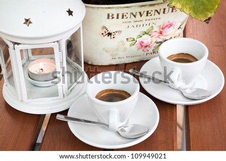 Two cups of espresso coffee on the table in the garden cafeteria restaurant. Decorative lamp and green leaf in the background. White cups with silver spoons. - stock photo