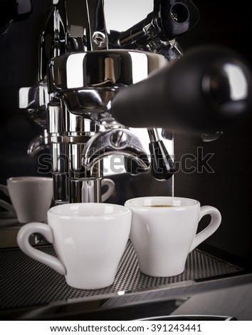 two cups of espresso poured from a espresso machine