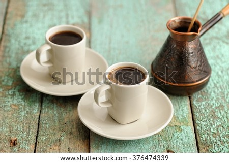 Two cups of fresh black coffee and copper cezve on old wooden table - stock photo
