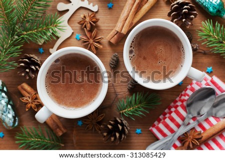 Two cups of fresh hot cocoa or hot chocolate on wooden christmas background, top view - stock photo