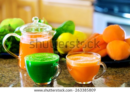 Two cups of fresh vegetable juice on kitchen counter with vegetables in background. Kale, spinach, cucumber, carrots, apples, lemons, lime, oranges. - stock photo