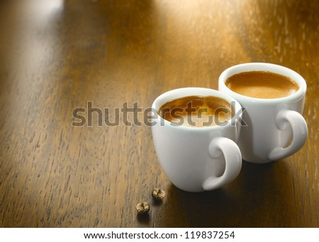 Two cups of freshly brewed espresso coffee with two single coffee beans on a textured wooden table top with copyspace