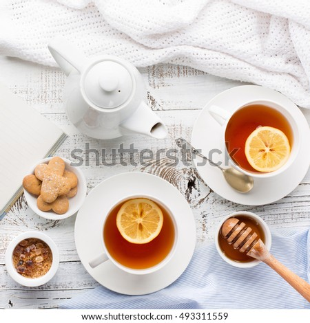 Two cups of hot black tea, lemon, homemade cookies and honey on white rustic wooden background. Breakfast concept. Top view, flat lay style
