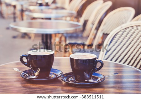 two cups of hot chocolate or coffee cappuccino on the table in cafe, close up, vintage style - stock photo