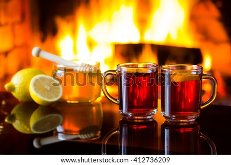 Two cups of hot drink wine tea, bowl of honey and lemon in front of warm fireplace. Magical relaxed cozy atmosphere near fire. - stock photo