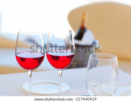 two cups of red wine and bottle in background on ice bucket - stock photo