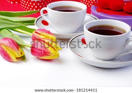 Two cups of tea and fresh red tulips  - stock photo