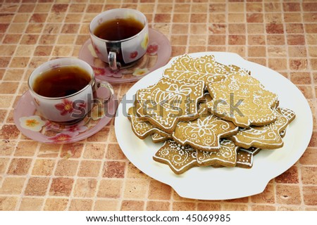 Two cups of tea and gingerbread cookies on the plate