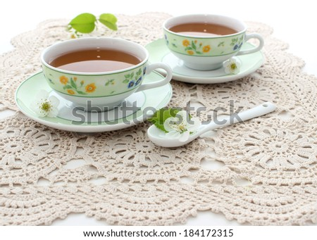 two cups of tea on beautiful napkin - stock photo