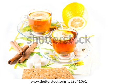 Two cups of tea with lemon and cinnamon on transparent saucers