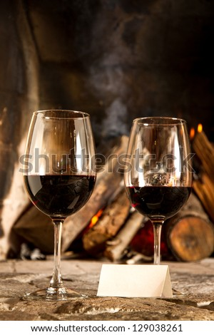 Two cups of wine with fire on the background, romantic meal. Love. Write your own message. - stock photo
