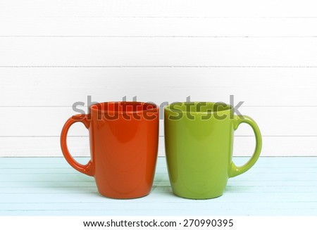 two cups on bright wooden background - stock photo