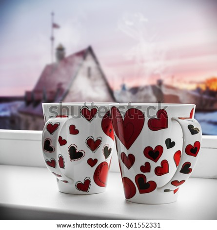 two cups with hearts on the window. It can be used for Valentine's Day greetings - stock photo
