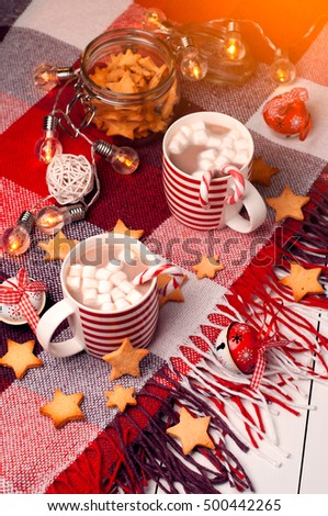 Two cups with hot chocolate and marshallow. Red plaid, ginger peonie in the form of stars, glowing lights. Vintage Christmas toys.