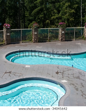 Two curvy shaped hot springs pools with treed background - stock photo
