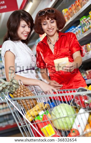 Two customers in supermarket. Cheese choice - stock photo