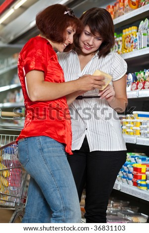 Two customers in supermarket. Focus on the girl in the white. - stock photo