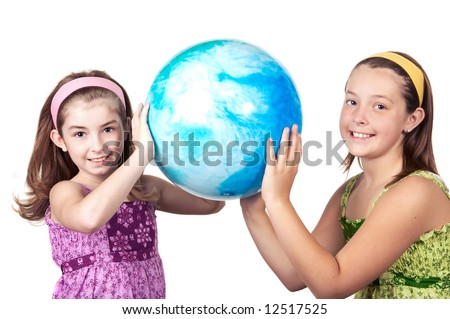 Two cute adolescent girls holding a big blue ball that looks like the world - stock photo