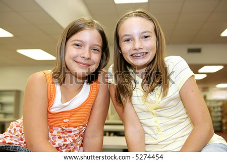 Two cute adolescent girls in the school library.