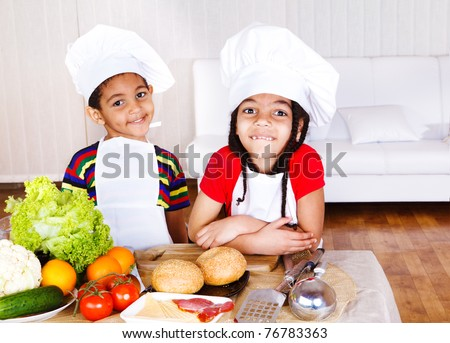 Two cute african american little cooks, ingredients for sandwich in front of them - stock photo