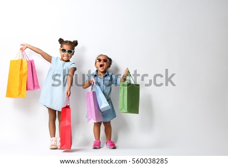 Two cute African girls with shopping bags on white background