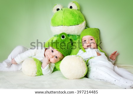 two cute babies lying in frog hats with a soft toy - stock photo