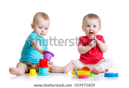 Two cute babies playing with cup toys. Children toddlers girl and boy sitting on floor, isolated on white background. - stock photo