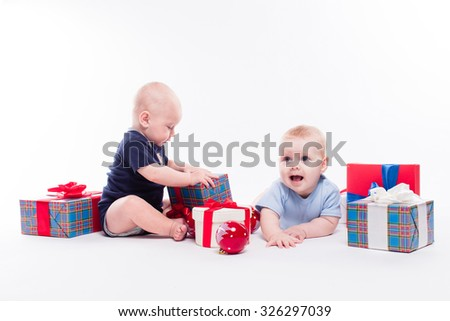 Two cute baby sitting on white background among the Christmas balls and red and blue gifts with smiles on their faces, picture with depth of field - stock photo
