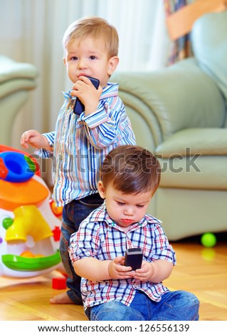 two cute baby toddlers explore mobile phones at home - stock photo