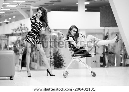 Two cute beautiful girls in dresses with shopping trolley and bag indoor on shop background black and white, horizontal picture - stock photo