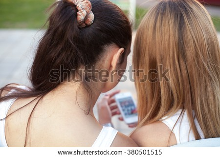 Two cute beautiful young women friends sitting on park bench on summer day, browsing social media pictures on smartphone, back view, focus on girls - stock photo
