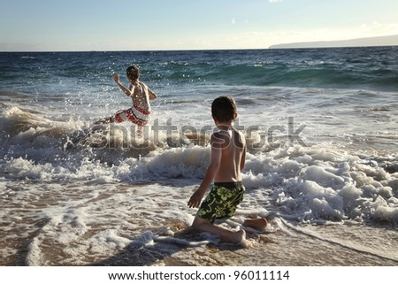two cute boys having fun at the ocean - stock photo