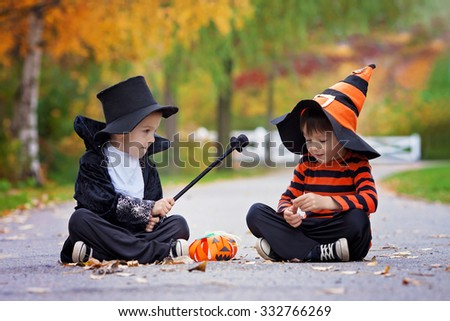 Two cute boys in the park with Halloween costumes, having fun, magician and witch - stock photo