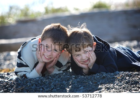 two cute boys lying on a rocky beach smiling at the camera - stock photo