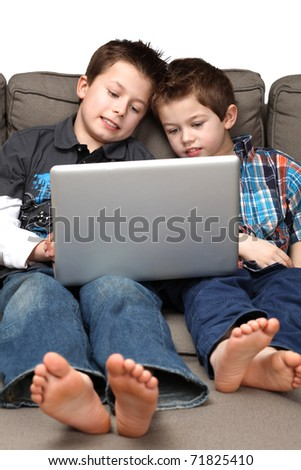 two cute boys on a couch surfing the internet - stock photo