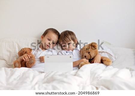 Two cute boys, sitting in bed, playing with tablet, teddy bears in their hands