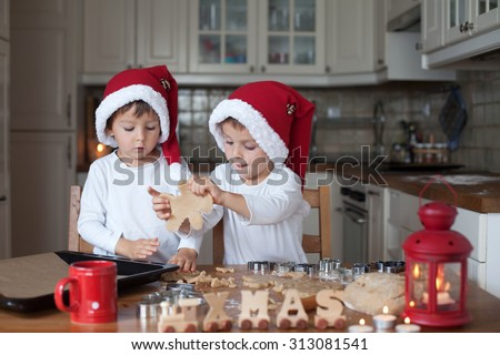 Two cute boys with santa hat, preparing cookies in the kitchen at home - stock photo