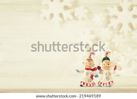 Two Cute Candy Cane Kid ceramic figurines from 1950s on Rustic White Wood Shelf and Background with Snowflakes Behind with blank room or space for copy, text, your words.  Vintage sepia - stock photo