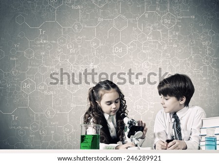 Two cute children at chemistry lesson making experiments
