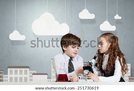 Two cute children at chemistry lesson making experiments - stock photo